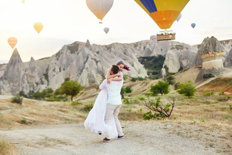 Paar in liefdetribunes op achtergrond van ballons in Cappadocia De man en een vrouw op heuvel bekijken een groot aantal vliegende stock afbeelding