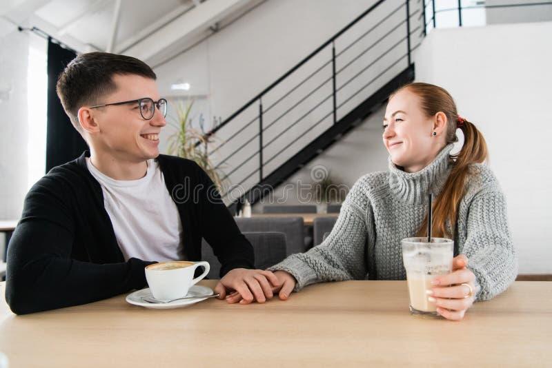 Paar in liefdezitting in koffie die elkaar bekijken en handen houden royalty-vrije stock afbeeldingen