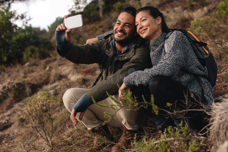 Paar in liefdezitting op bergsleep en het nemen selfie royalty-vrije stock fotografie