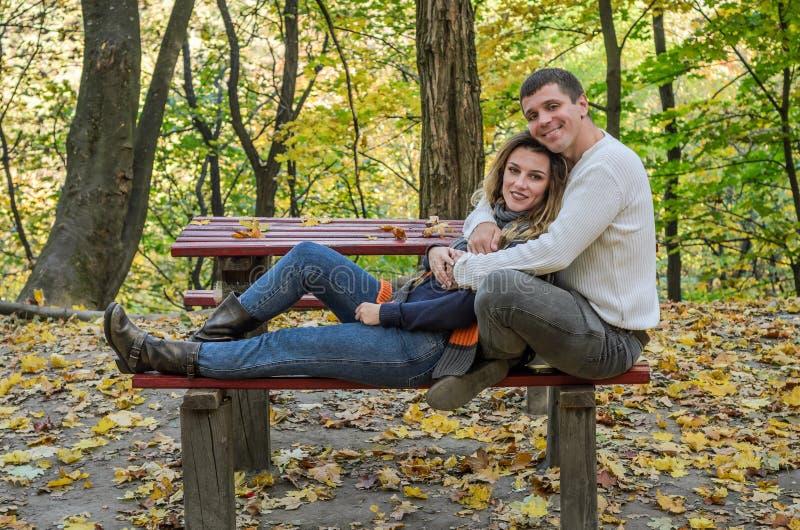 Paar in liefdezitting op een bank in het de herfstpark onder de gele gevallen bladeren stock afbeelding
