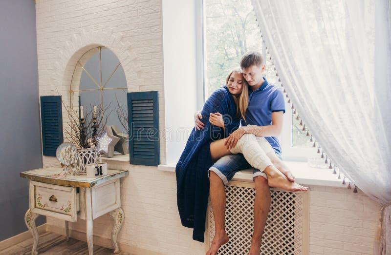 Paar in liefdezitting thuis op het venster Het tedere houden van embr royalty-vrije stock afbeeldingen