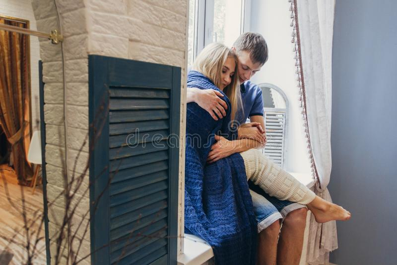 Paar in liefdezitting thuis op het venster Het tedere houden van embr royalty-vrije stock fotografie