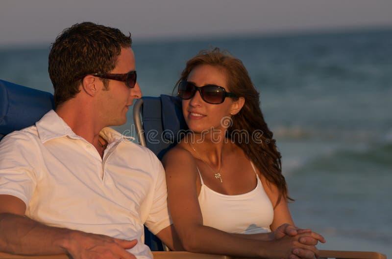 Paar in ligstoelen stock foto's