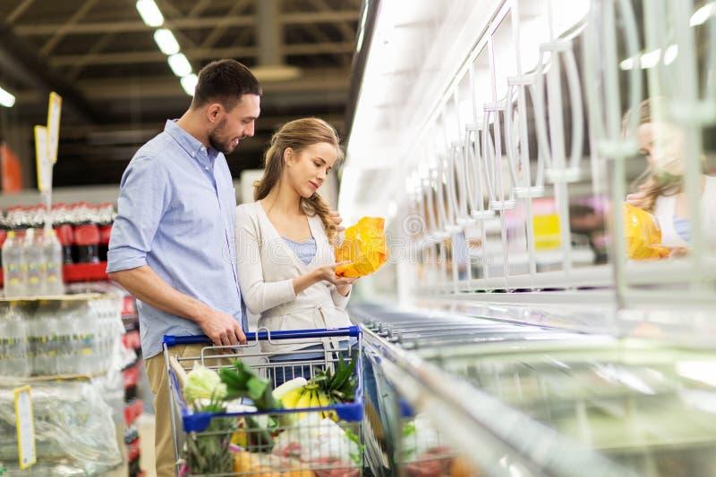 Paar met boodschappenwagentje het kopen voedsel bij kruidenierswinkel stock afbeelding