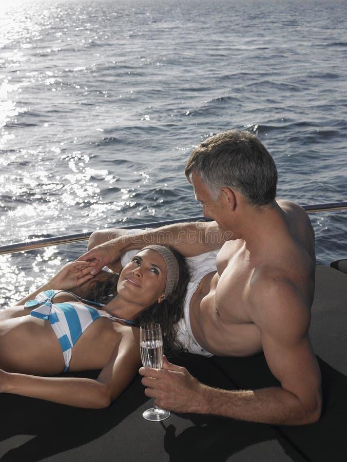 Paar met Champagne Flute Relaxing On Yacht stock fotografie