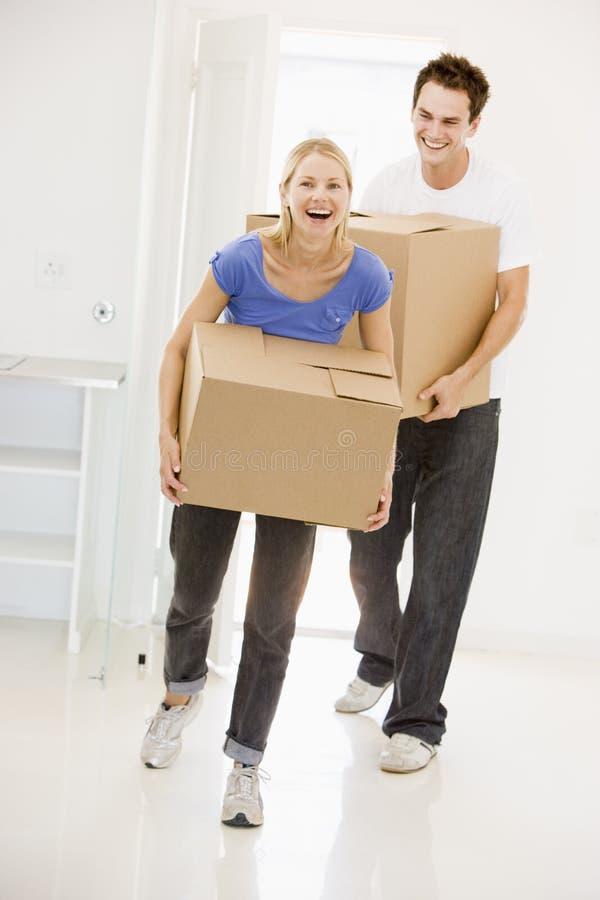 Paar met dozen die zich in het nieuwe huis glimlachen bewegen