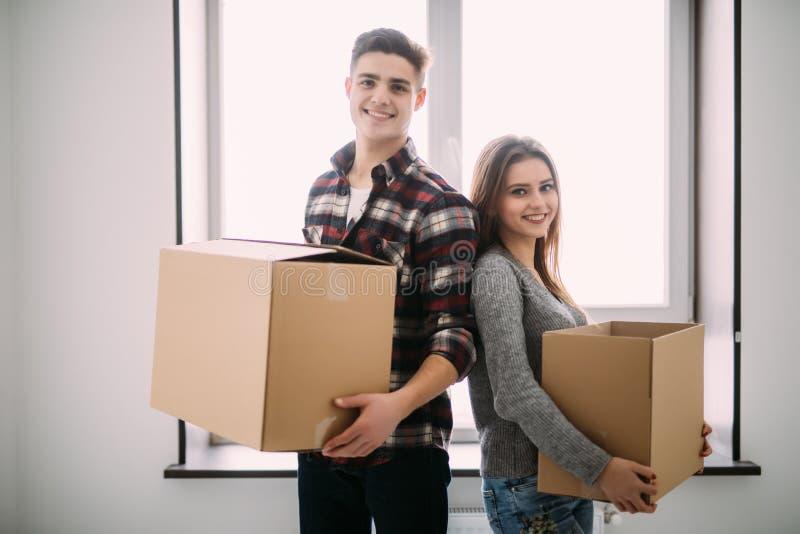 Paar met dozen die zich in het nieuwe huis glimlachen bewegen Jong paar bij het bewegen van dag royalty-vrije stock foto's