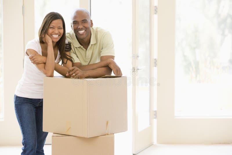 Paar met dozen in het nieuwe huis glimlachen