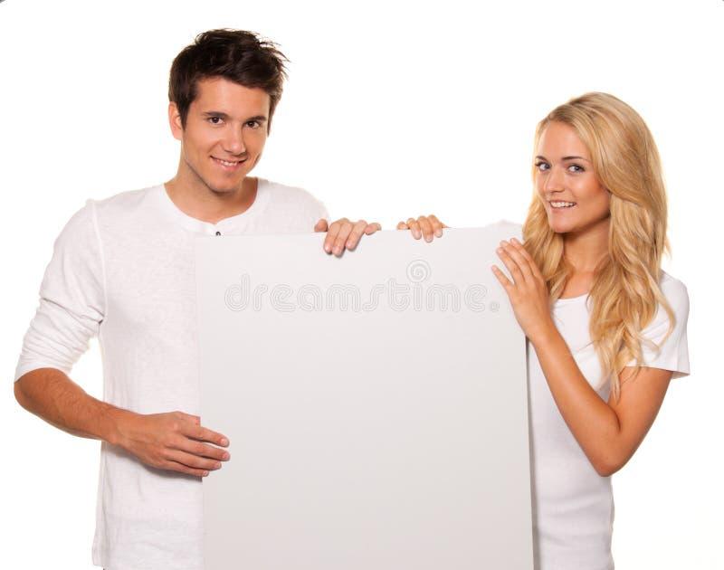 Paar met een lege affiche om het openen te adverteren stock fotografie