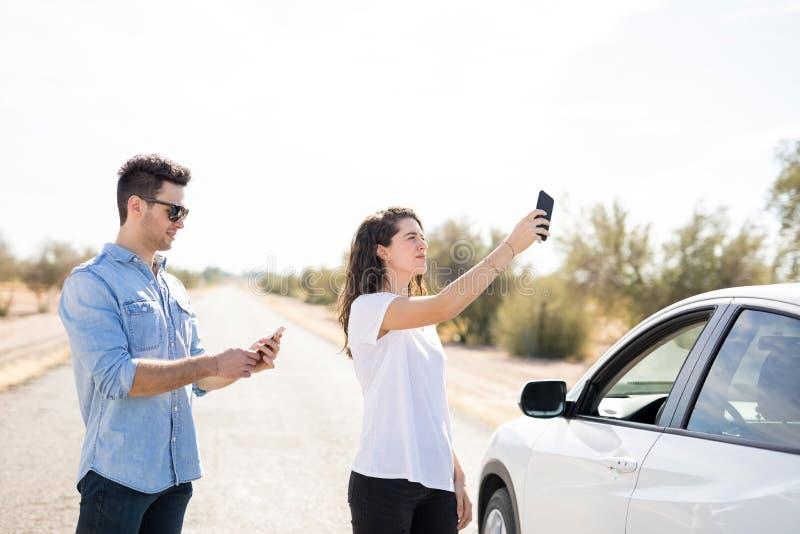 Paar met gebroken auto die naar telefoondekking zoeken royalty-vrije stock afbeelding