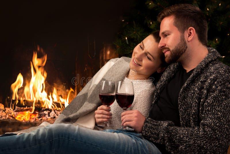 Paar met glas wijn bij open haard stock fotografie