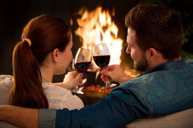 Paar met glas wijn bij open haard royalty-vrije stock afbeelding