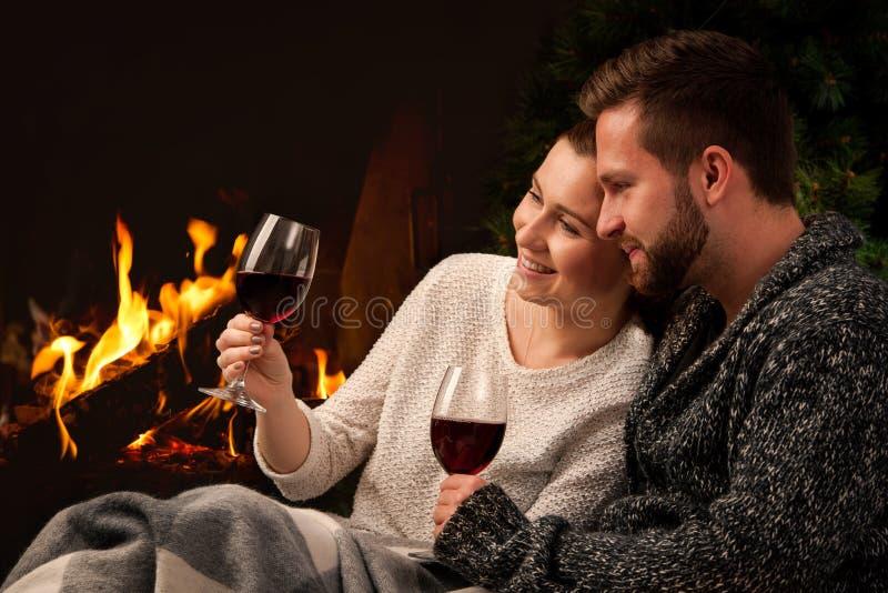 Paar met glas wijn bij open haard stock foto