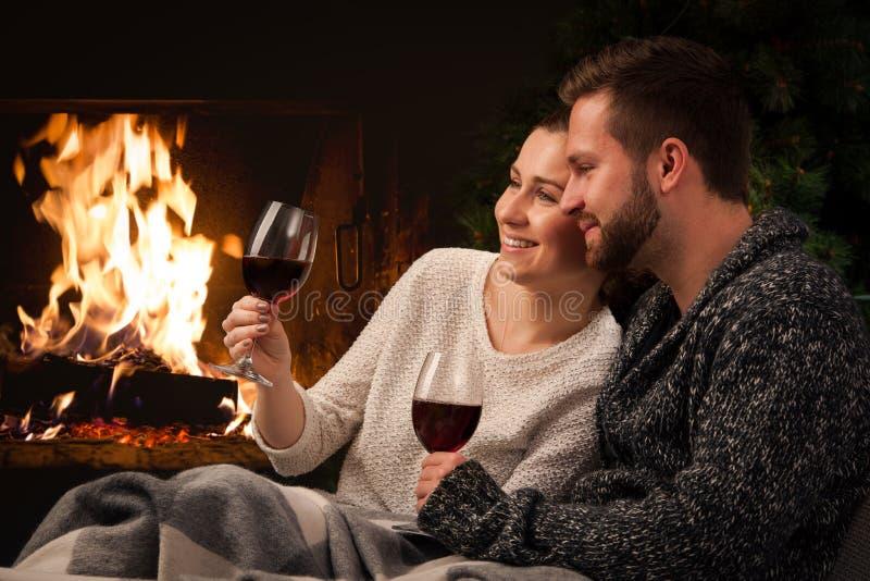 Paar met glas wijn bij open haard stock afbeeldingen