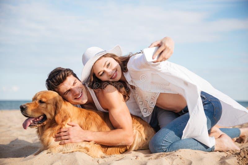 Paar met hond die selfie gebruikend smartphone op het strand spreken royalty-vrije stock afbeelding