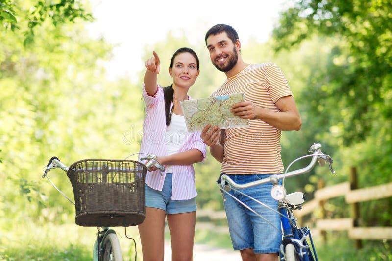 Paar met kaart en fietsen bij land in de zomer stock fotografie