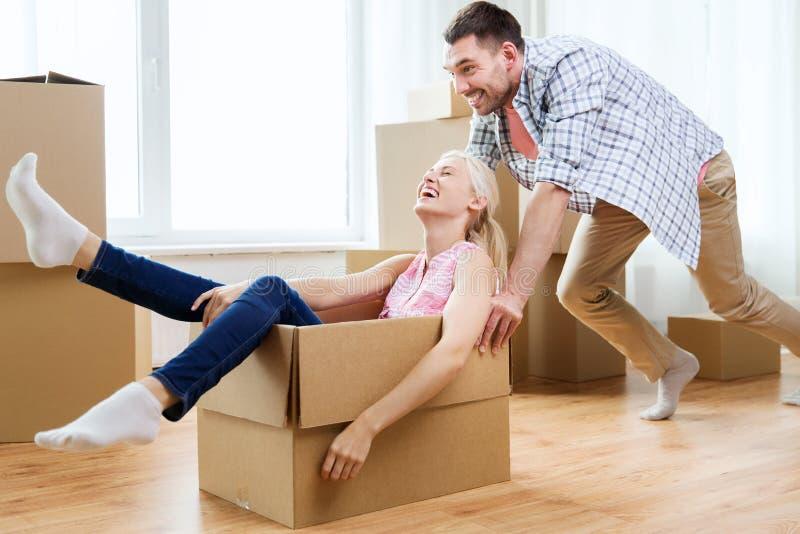 Paar met kartondozen die pret hebben bij nieuw huis stock afbeeldingen