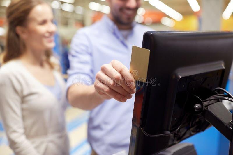 Paar met klantenkaart bij opslag zelf-controle stock foto