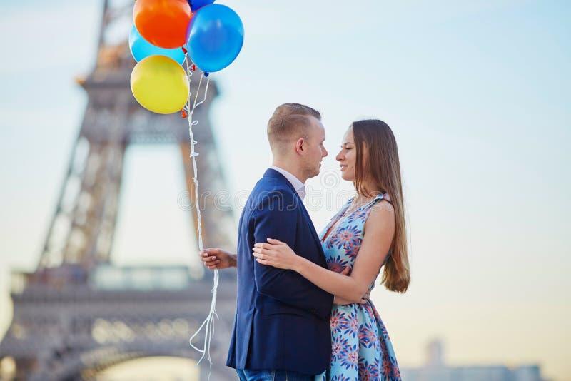 Paar met kleurrijke ballons dichtbij de toren van Eiffel stock afbeeldingen