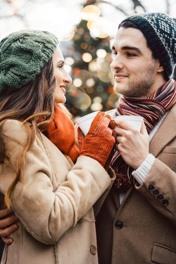 Paar met koppen van overwogen wijn op Kerstmismarkt royalty-vrije stock foto's