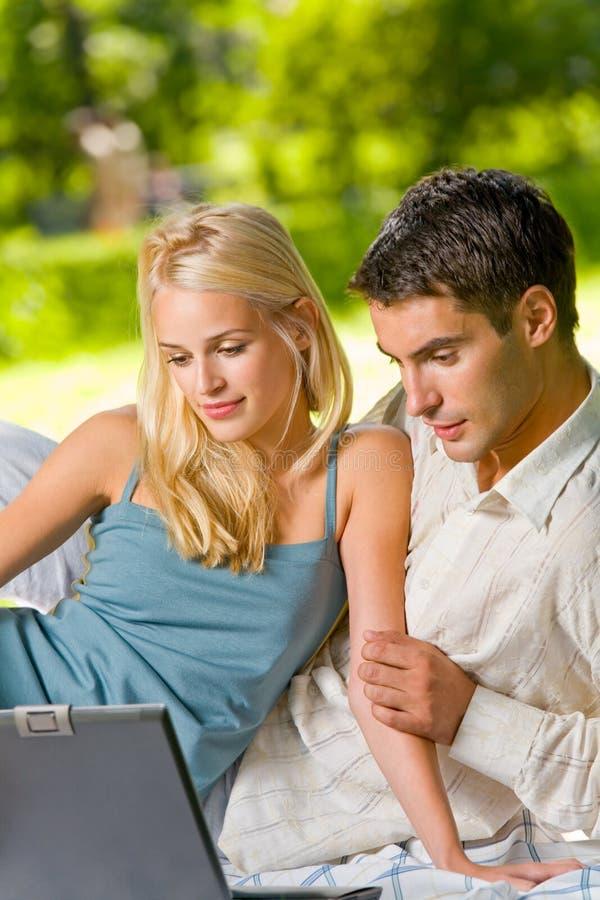 Paar met laptop bij picknick royalty-vrije stock foto's