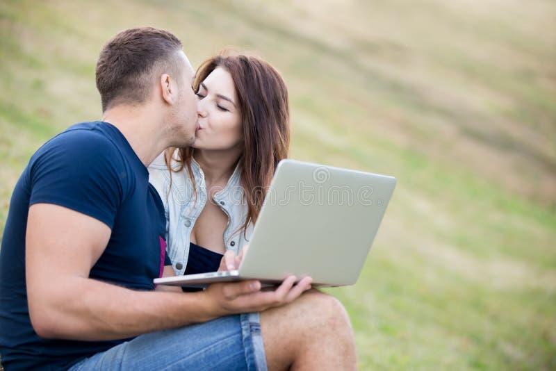 Paar met laptop het kussen in park royalty-vrije stock foto's