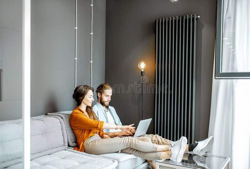Paar met laptop thuis stock fotografie