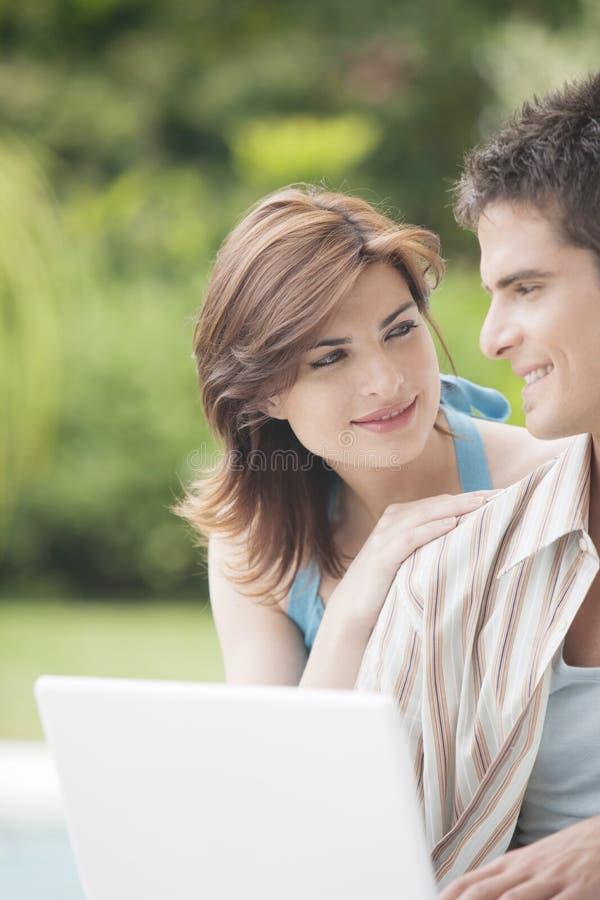 Paar met Laptop in Tuin stock foto