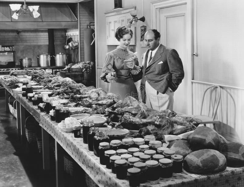 Paar met lijst in voedsel voor vakantiemaaltijd wordt behandeld (Alle afgeschilderde personen leven niet langer en geen landgoed  stock fotografie