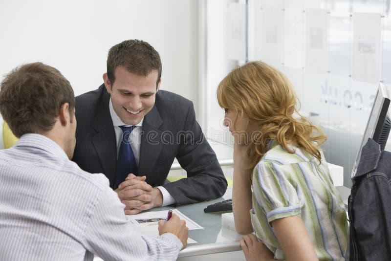 Paar met Makelaar in onroerend goed In Office stock afbeeldingen