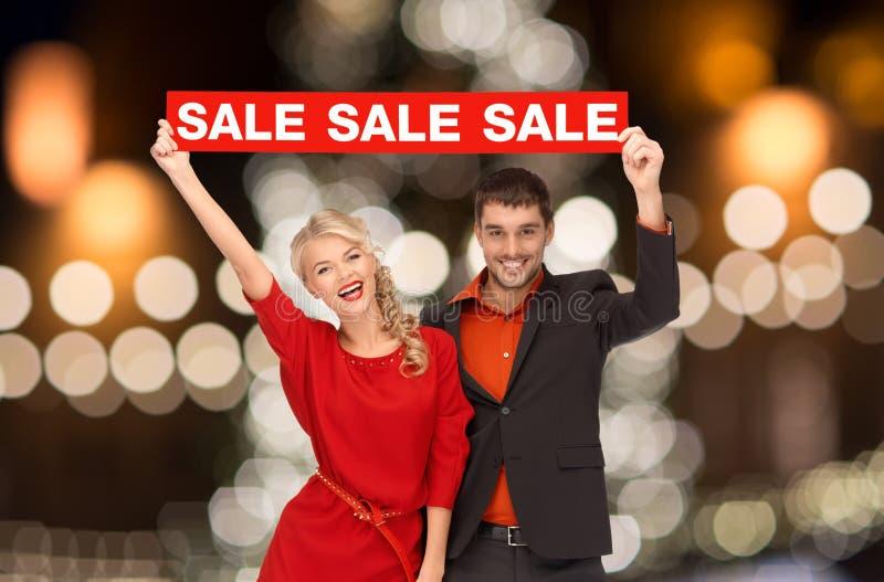 Paar met rood verkoopteken over Kerstmislichten royalty-vrije stock afbeelding