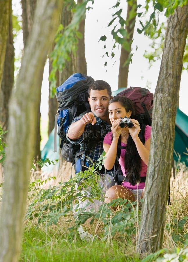 Paar met rugzakken en verrekijkers in openlucht stock foto's
