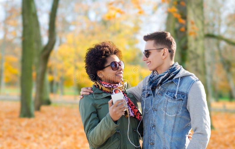 Paar met smartphone en oortelefoons in de herfst royalty-vrije stock afbeelding