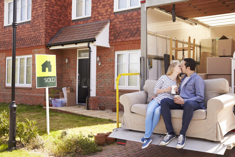 Paar met Sofa On Tail Lift Of-Verwijderingsvrachtwagen die zich naar huis bewegen stock fotografie