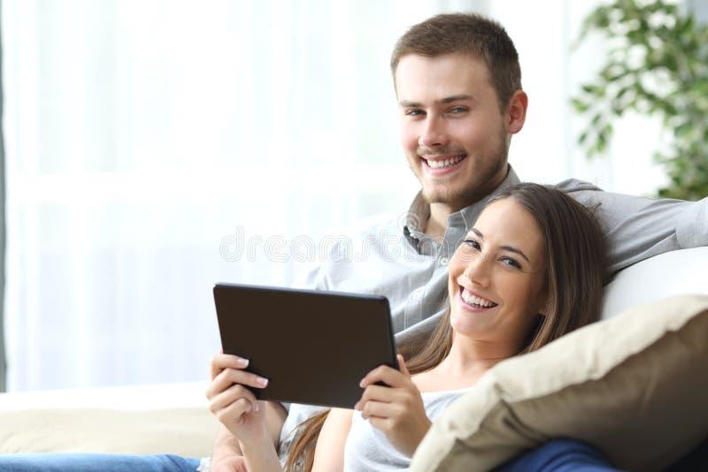 Paar met tablet die thuis stellen stock afbeeldingen