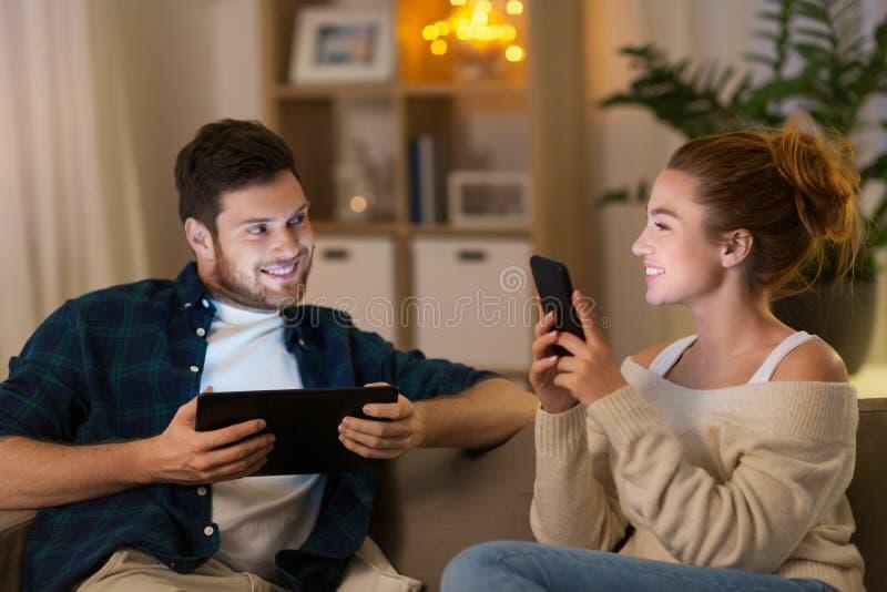 Paar met tabletcomputer en smartphone thuis royalty-vrije stock fotografie