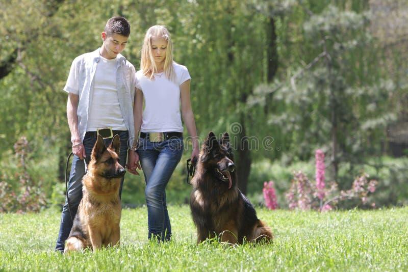 Paar met twee honden op natuurlijke achtergrond royalty-vrije stock afbeelding