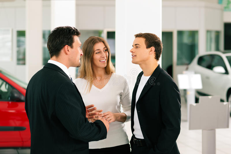 Paar met verkoper bij autohandelaar