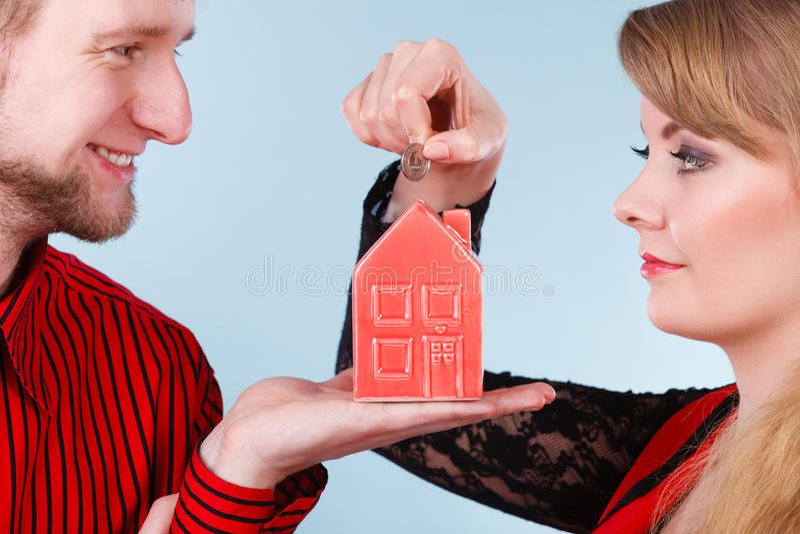 Paar met weinig huis en zilveren muntstuk stock afbeeldingen