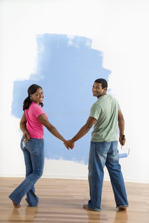 Paar naast helft-geschilderde muur. royalty-vrije stock afbeeldingen