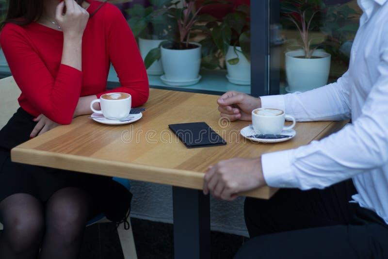 Paar, ochtendkoffie in de cafetaria, op de lijst een rekening voor de diensten, jongen en meisje, mededeling, ontbijt stock fotografie