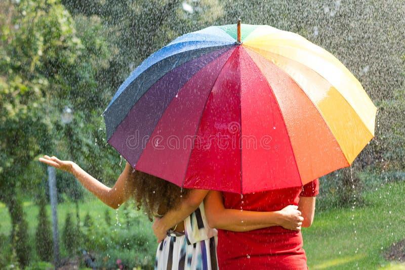 Paar onder regenboogparaplu royalty-vrije stock foto's