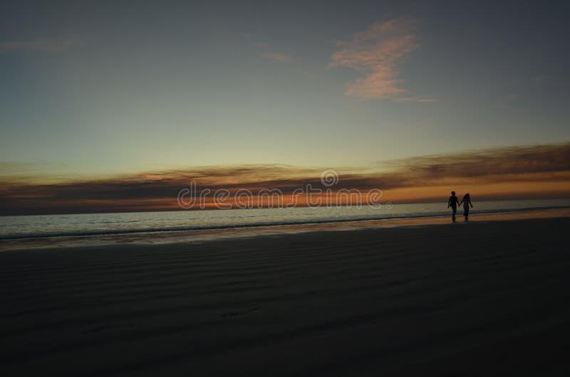 Paar onder zonsondergang stock foto's