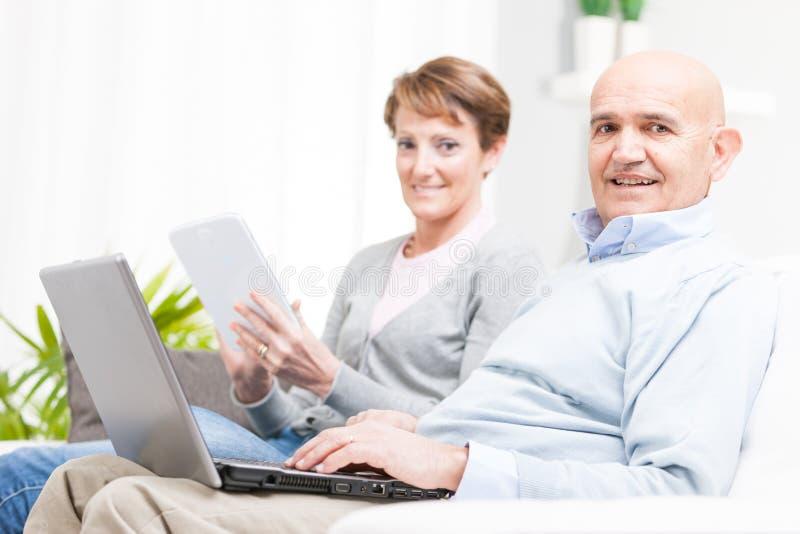 Paar ontspannen het op middelbare leeftijd met mobiele apparaten stock foto's