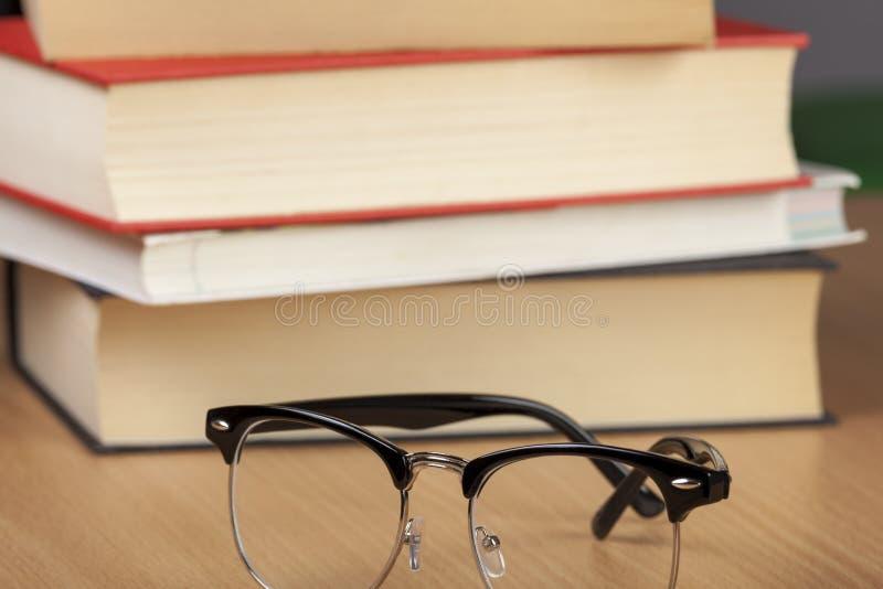 Paar oogglazen naast een stapel van boeken stock fotografie