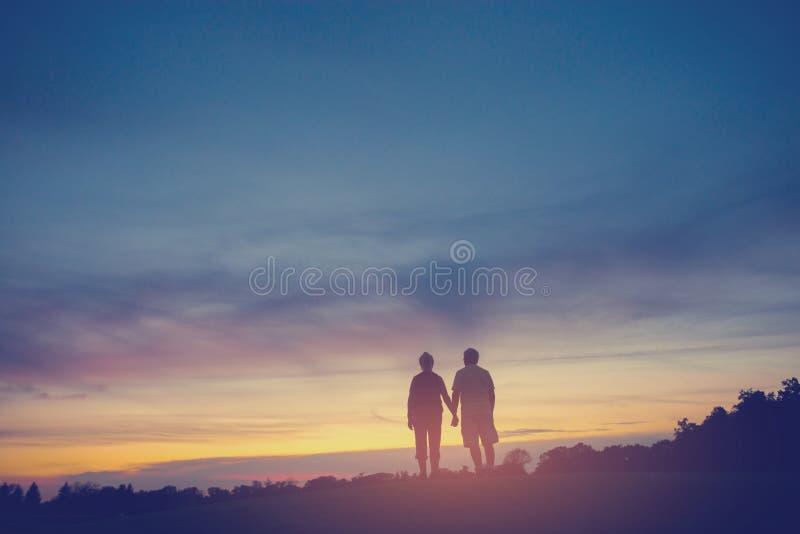 Paar op achtergrond van zonsondergang stock fotografie
