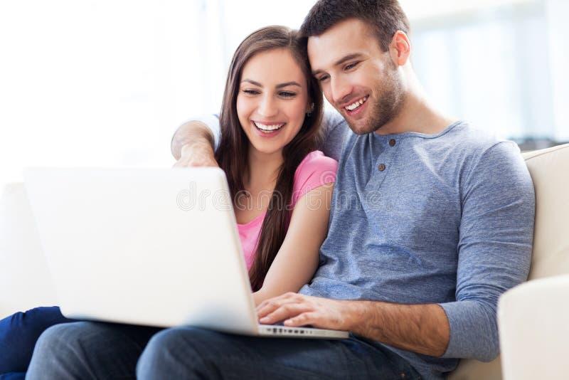 Paar op bank met laptop royalty-vrije stock afbeelding