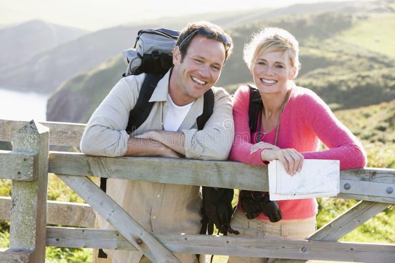 Paar op cliffside die in openlucht op traliewerk leunt royalty-vrije stock fotografie