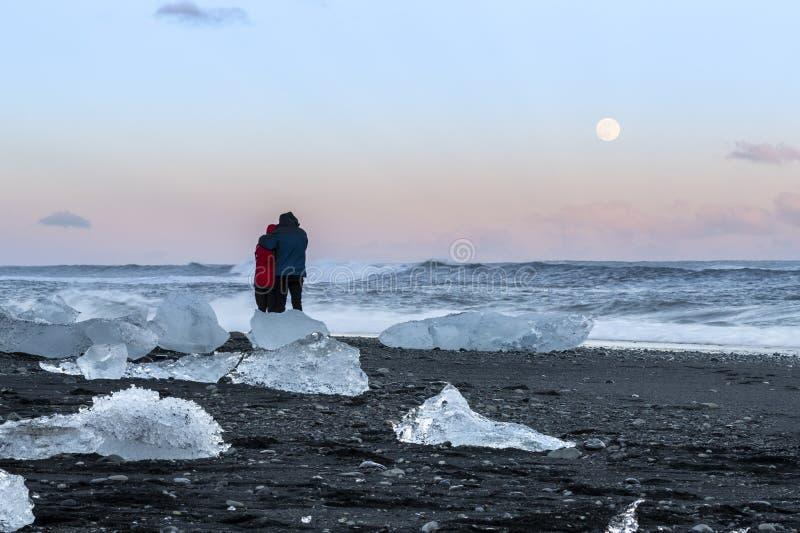 Paar op diamantstrand, Jokulsarlon, IJsland stock foto's