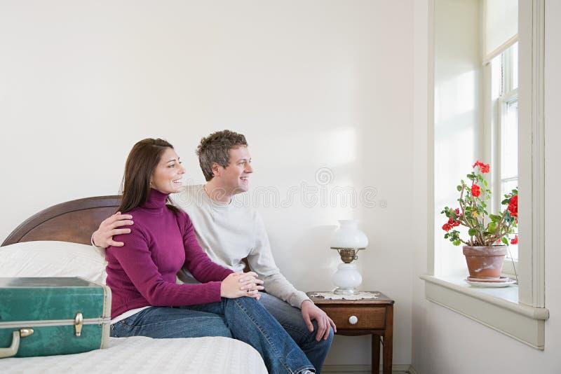 Paar op een bed wordt gezeten dat royalty-vrije stock fotografie